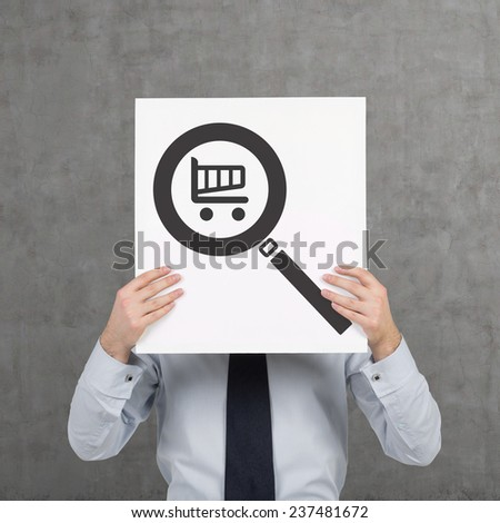 businessman holding poster with magnifier with trolley - stock photo