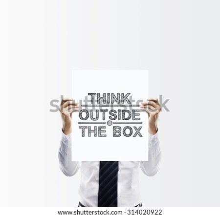 businessman holding poster with think outside the box - stock photo