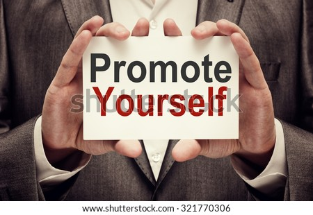 Businessman holding Promote yourself card - stock photo