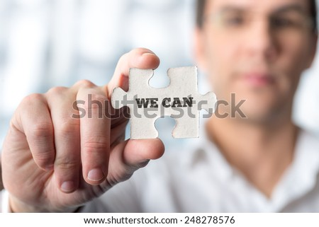 Businessman holding puzzle piece with We can text in a conceptual image for successfully overcoming problems and challenges, positive attitude and providing the service. - stock photo