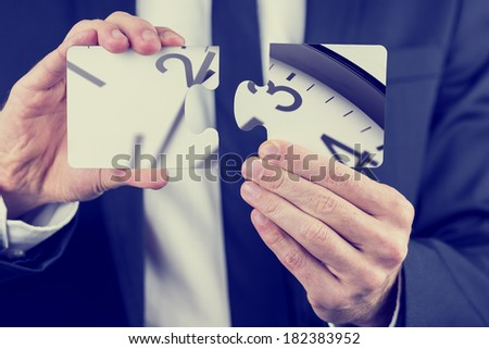 Businessman holding puzzle pieces depicting sections of the dial of a clock conceptual of deadlines, time management and problem solving, close up of his hands. - stock photo