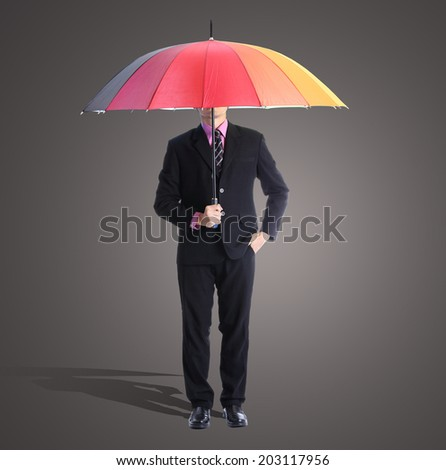 Businessman holding rainbow umbrella in studio