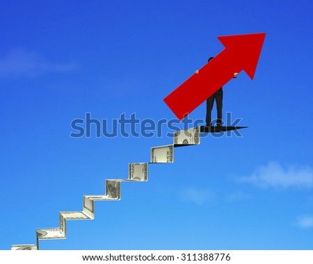 Businessman holding red arrow sign on top of money stairs, with blue sky background. - stock photo