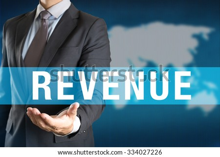 Businessman holding REVENUE word with world background - stock photo