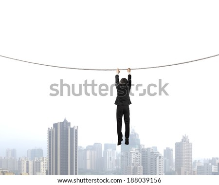 Businessman holding rope and hanging  with city view - stock photo