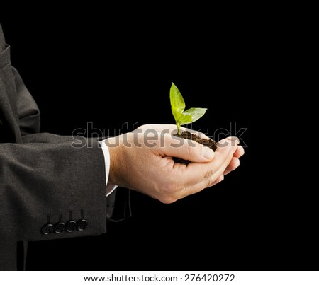 Businessman holding seedling in his hands on black background Environment and nature protection concepts - stock photo
