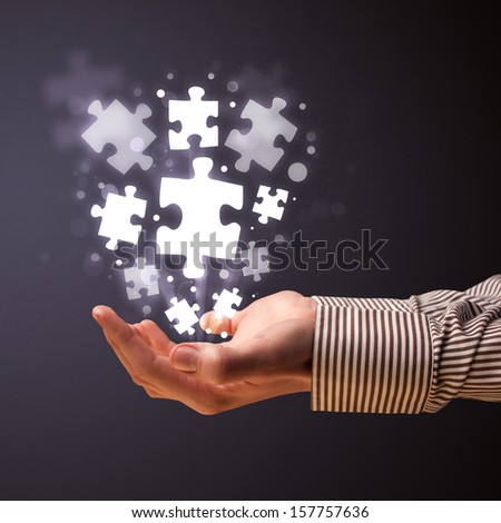 Businessman holding shining puzzle pieces in his hand - stock photo