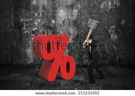 Businessman holding sledgehammer hitting red percentage sign with dark concrete room background - stock photo