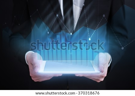 businessman holding tablet with graphs on screen.businessman holding tablet computer with graphs on screen. business concept. technology concept. business concept. technology concept. - stock photo