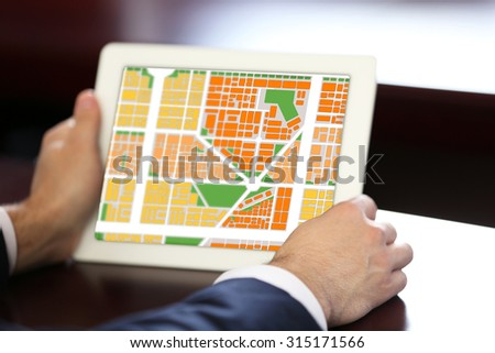 Businessman holding tablet with map gps navigation application - stock photo