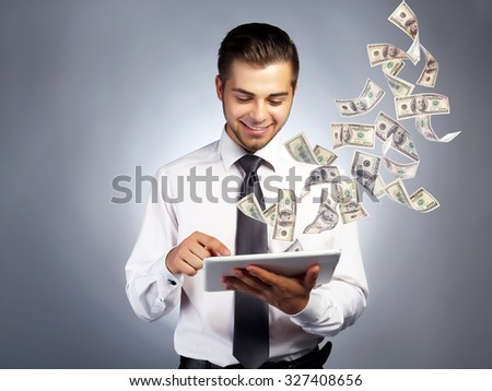 Businessman holding tablet with money fly out of it - stock photo