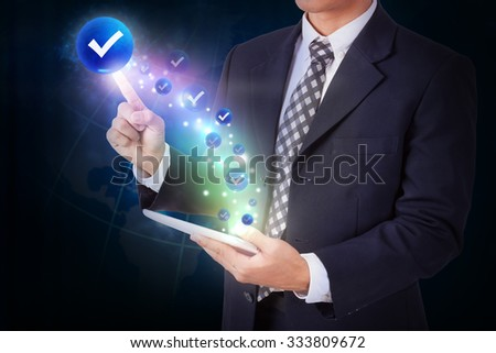 Businessman holding tablet with pressing check mark icon button. internet and technology concept - stock photo