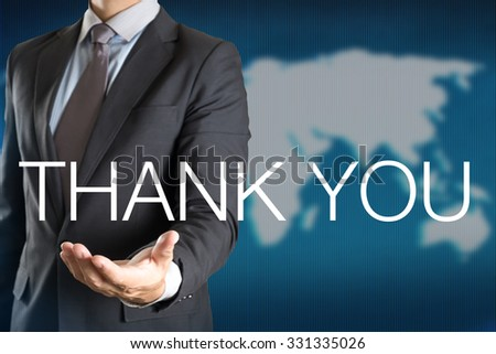 Businessman holding THANK YOU word with world background - stock photo