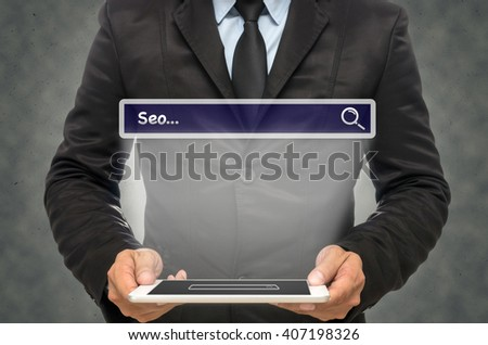 "Businessman holding the tablet with browsing of Internet searching ""Seo"" bar on the wall background, Internet concept"