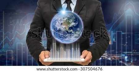 Businessman holding the tablet with earth and building on Trading graph on the cityscape at night and world map background,Elements of this image furnished by NASA - stock photo