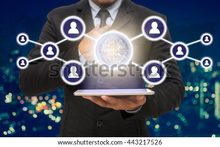 Businessman holding the tablet with the Social media symbol on Blurred Photo bokeh of cityscape, Elements of this image furnished by NASA, Business network concept