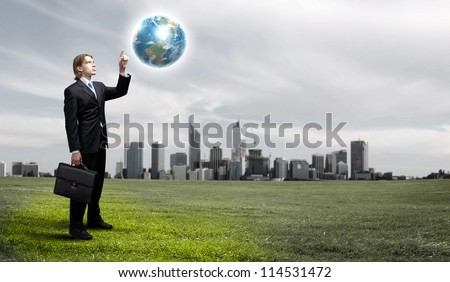 Businessman holding the world in the palm of his hand.Elements of this image furnished by NASA. - stock photo