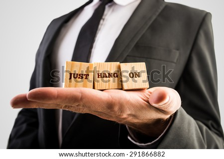 Businessman holding three wooden cubes in the palm of his hand with the motivational words - Just hang on - - stock photo