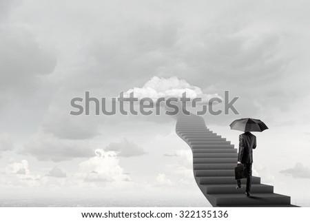 Businessman holding umbrella and waking on career ladder - stock photo