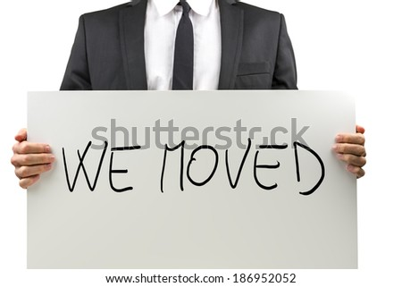 Businessman holding white board with We moved sign on it. - stock photo