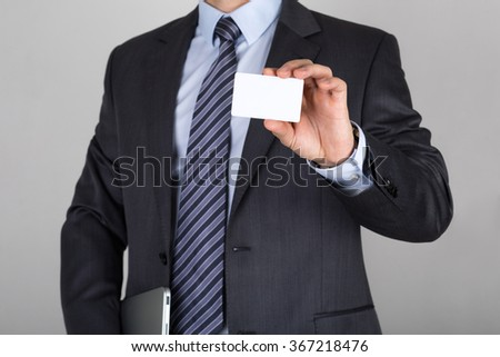 Businessman holding white business card. Business meeting or presentation concept - stock photo
