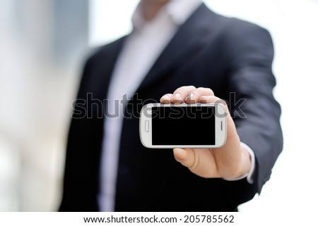 businessman holding white mobile smart phone with black display in hand - stock photo