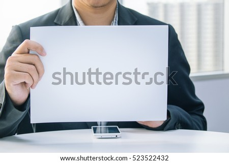 Businessman holding white paper in the office