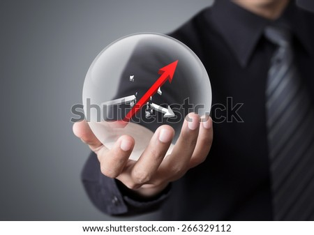 Businessman holds crystal ball with rising red graph and broken white graph - stock photo