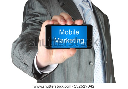 Businessman holds smart phone with mobile marketing words on its screen isolated on white background. - stock photo
