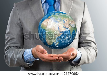businessman holds up a planet Earth. Elements of this image furnished by NASA