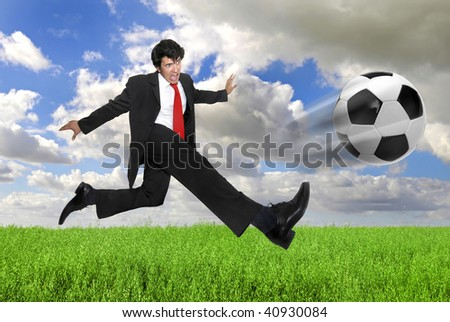 Businessman in a acrobatic pose kicking a soccer ball in a green field - stock photo