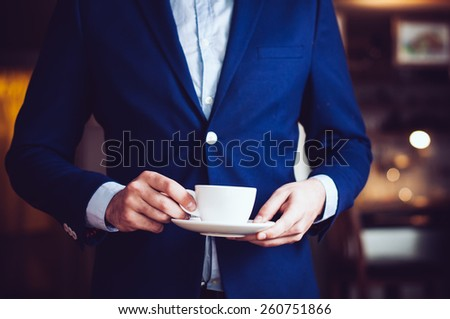 Businessman in a blue jacket standing with a cup of coffee in the cafe, close-up - stock photo