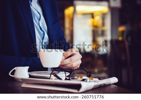 Businessman in a blue jacket with a cup of coffee, reading glasses, newspaper and smartphone in a cafe at the table, close-up - stock photo