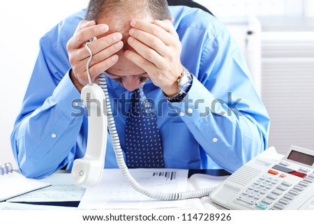 Businessman in a blue shirt having stress in the office - stock photo