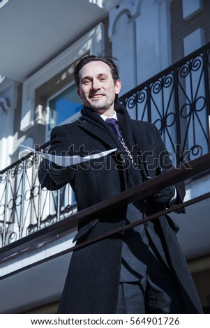 Businessman in a dark coat shows the working papers in the foyer of the building, the lower angle , day, outdoor