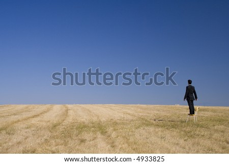 businessman in a field looking high to the future - stock photo