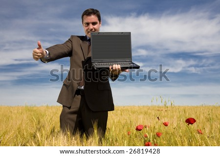 Businessman in a field showing his laptop - stock photo