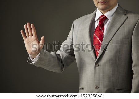 Businessman in a gray suit, white shirt and red tie on a gray background shows an empty hand