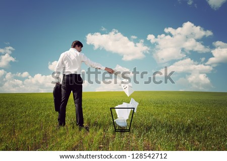 businessman in a green field with a blue sky throws papers in the trash - stock photo