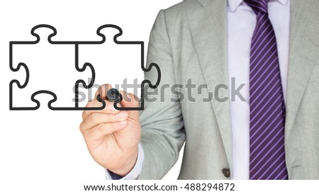 Businessman in a grey suit drawing two jigsaw pieces on a screen with a black pen on white