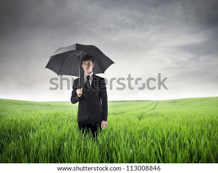 Businessman in a large field with an umbrella - stock photo