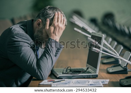 businessman in a panic and depression has her head  	 on the backdrop of the conference hall in the green range