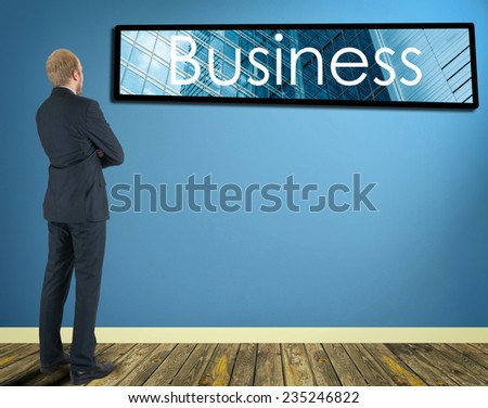 businessman in a room looking at a wall of which is the frame with inscription Business - stock photo