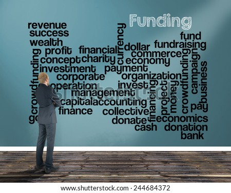 businessman in a room looking at a wall of which is the wordcloud related to funding - stock photo