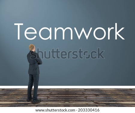 businessman in a room staring at the wall on which is the inscription: teamwork - stock photo