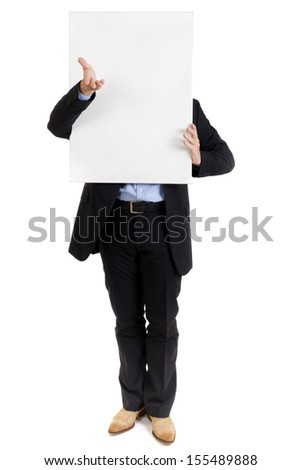 Businessman in a smart suit standing with a blank white sign held in front of his face gesturing with his hand for your attention, copyspace for your text or advertisement