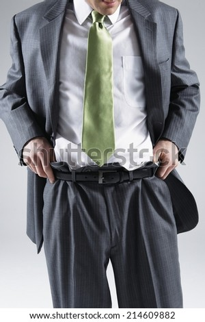 Businessman in a stylish green tie pulling up a pair of over sized suit trousers that are several sizes too large conceptual of weight loss through healthy eating, illness or stress at the office - stock photo