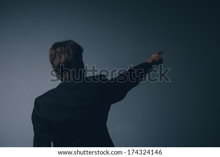 Businessman in a stylish suit standing with his back to the camera pointing ahead and calling your attention towards copy space on a grey background