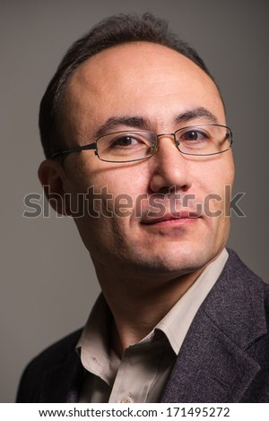 businessman in a suit and glasses on a dark background looking at the camera, age thirty-five, thirty-seven years