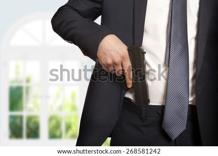 Businessman in a suit holding a gun  - stock photo